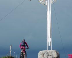 Foto Mountainbiker neben Gipfelkreuz