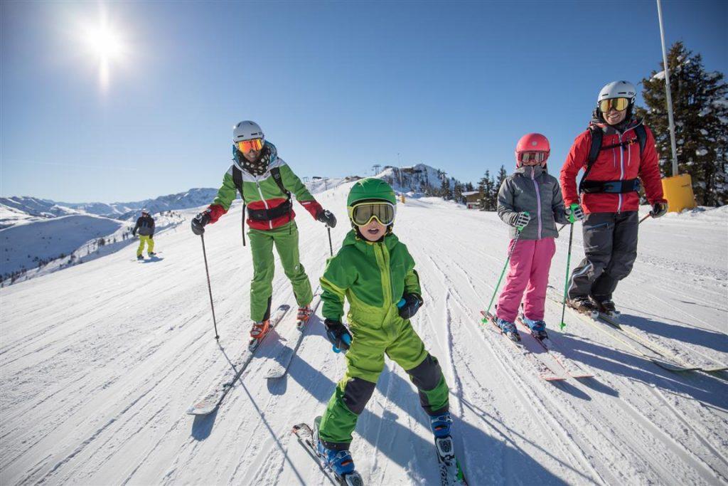 Kinder und Erwachsene beim Ski fahren